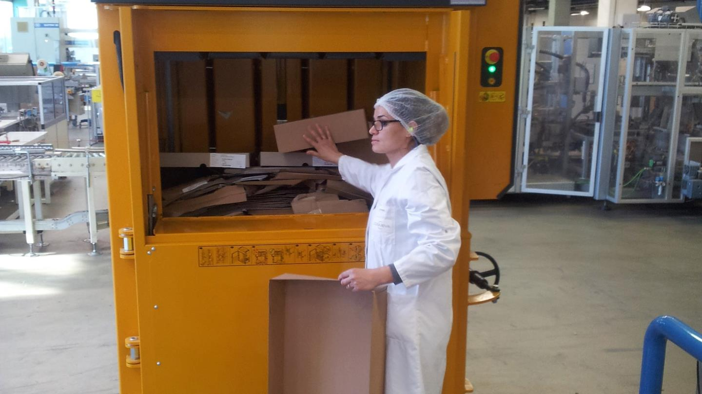Female employee with hairnet fills cardboard into Bramidan baler at Cosmeva