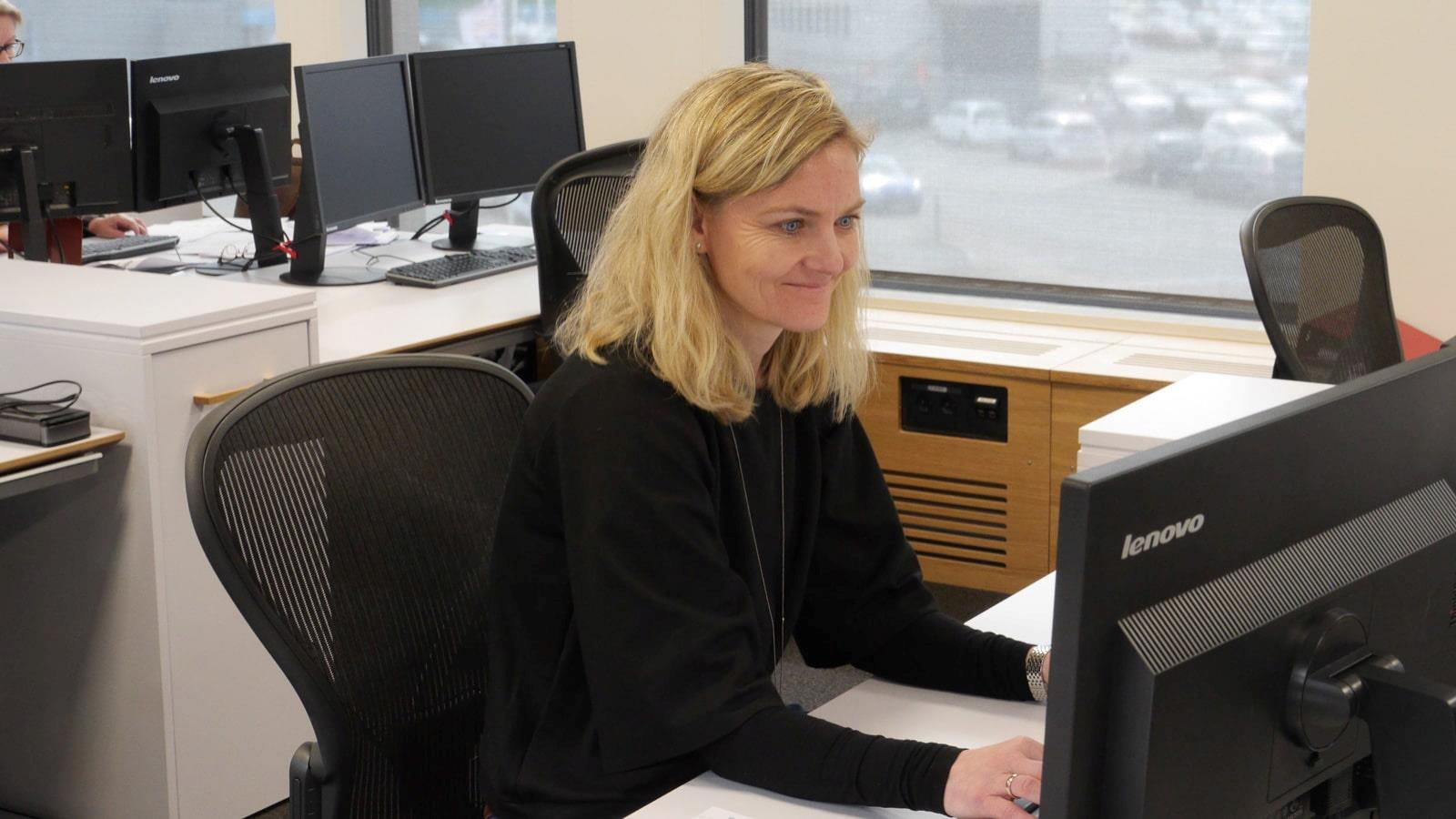 Blonde woman working at computer