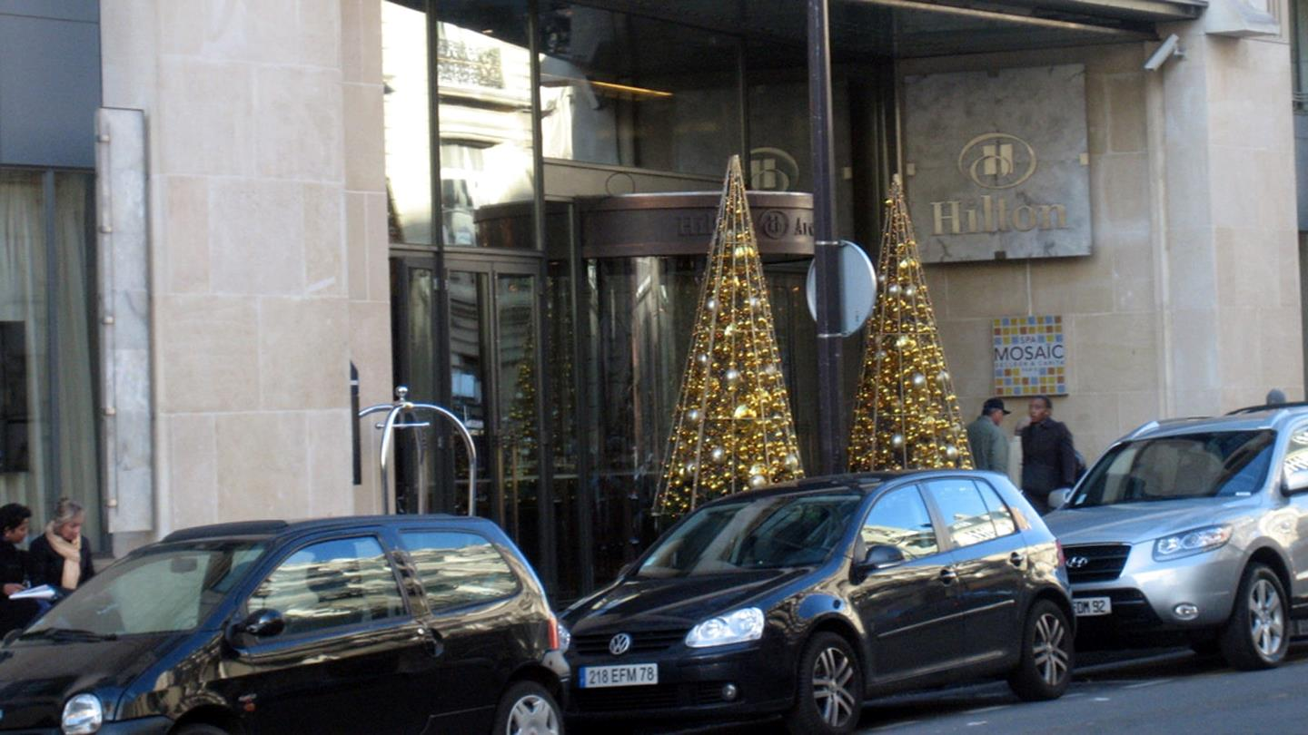 Two Christmas trees with golden decoration at Hilton Hotel entrance