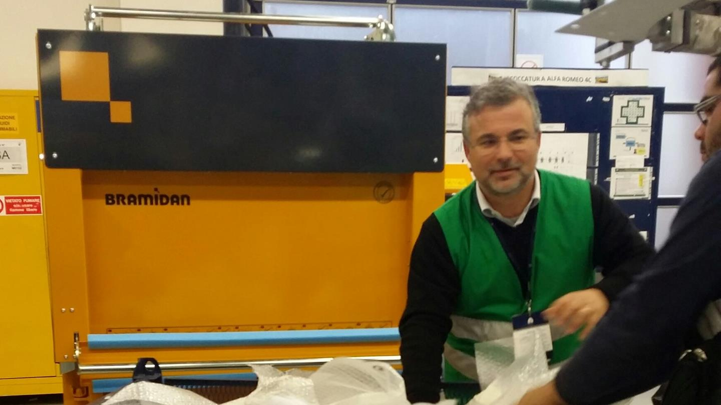 Man handles plastic waste next to yellow Bramidan baler