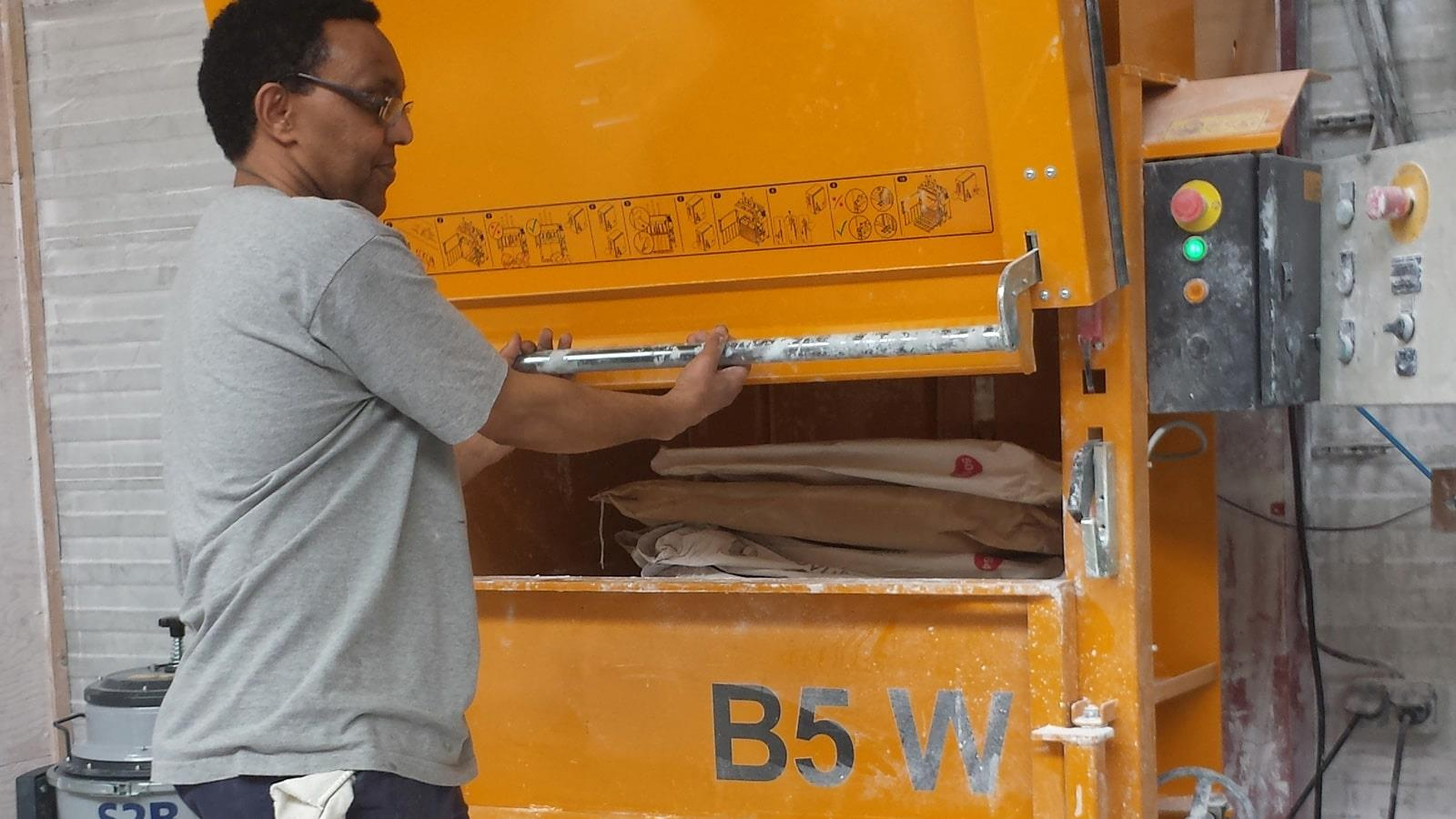 Nitta employee pulls ergonomical door handle to close baler door
