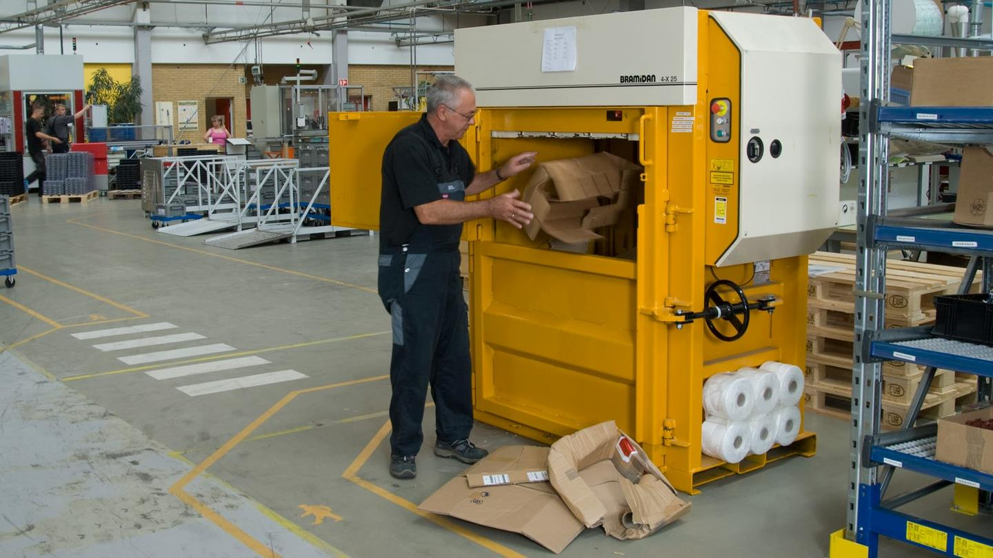 Sauer-Danfoss employee throws cardboard boxes into Bramidan baler