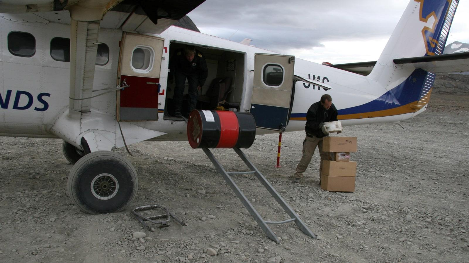 Boxes and a drum being unloaded from small airplane
